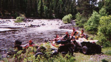 group of atv-ers relaxing on the bank of the river